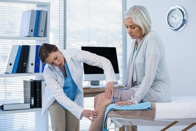 Arzt untersucht das knie des patienten