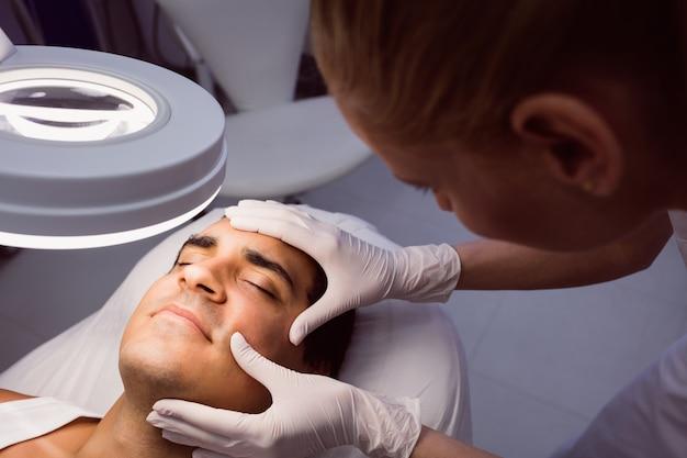 Arzt untersucht manngesicht für kosmetische behandlung