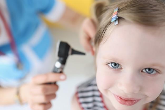 Arzt untersucht ohr mit otoskop für kleines lächelndes mädchen