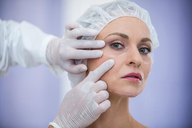 Arzt untersucht weibliche patienten gesicht für kosmetische behandlung