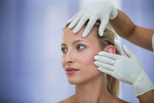 Arzt untersucht weibliche patienten gesicht von kosmetischen behandlung
