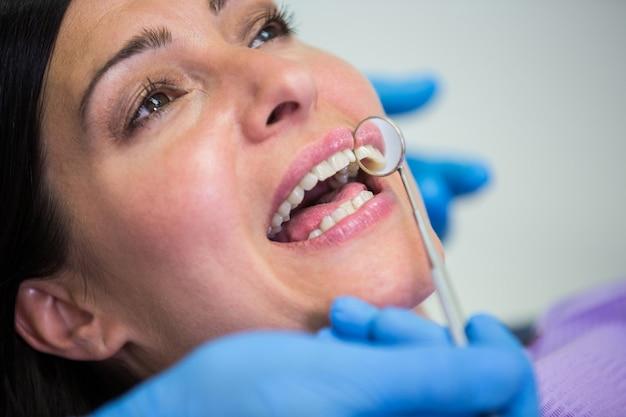 Arzt untersucht weibliche patientenzähne mit dem mundspiegel