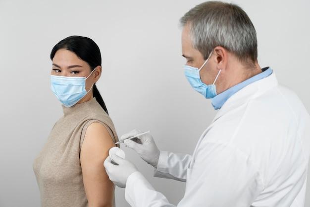 Arzt verabreicht einer patientin einen impfschuss