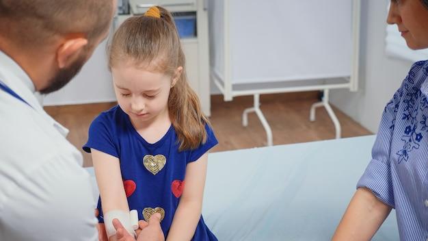 Arzt verbindet die verletzte hand des kindes, die in der arztpraxis sitzt. heilpraktiker arzt arzt facharzt für medizin, der gesundheitsdienste anbietet beratungsbehandlung im krankenhausschrank