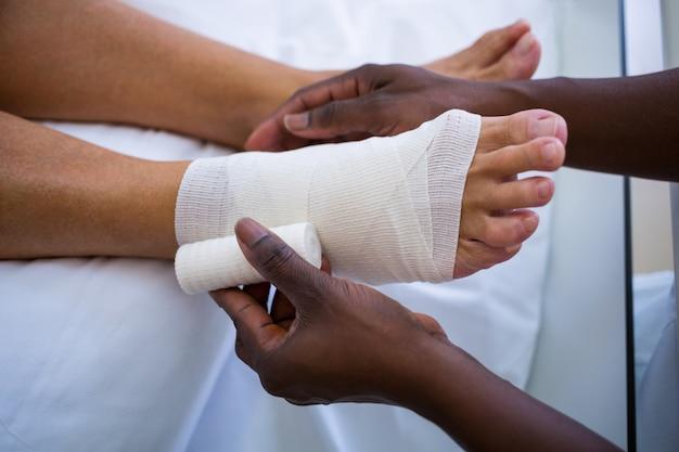 Arzt verbindet patienten bein