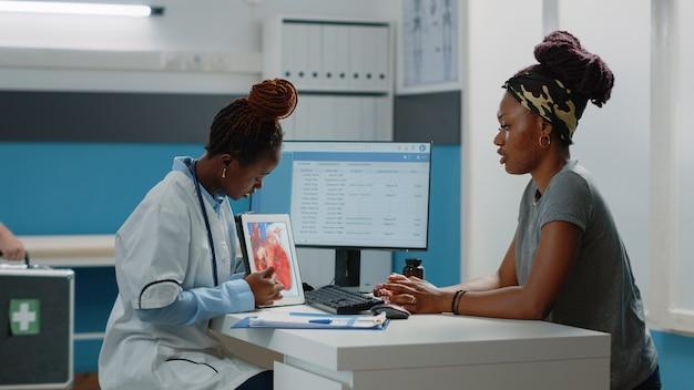 Arzt zeigt auf tablet mit herz-kreislauf-figur