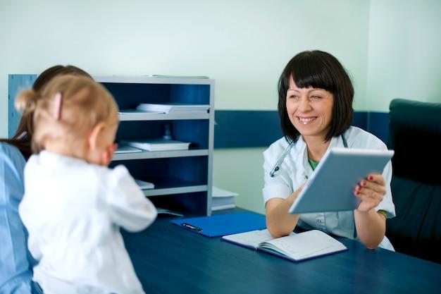 Arzt zeigt die medizinischen ergebnisse der mutter auf der tablette