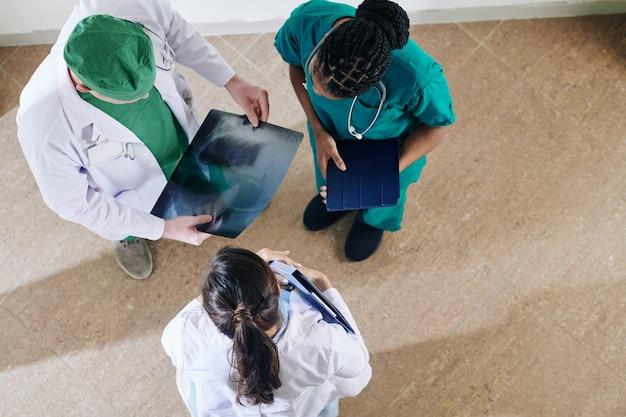 Arzt zeigt kollegen die röntgenaufnahme des patienten in der brust und fragt nach ihrer meinung, ansicht von oben