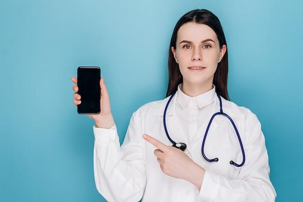 Arzt zeigt mit dem finger auf den mobilen bildschirm, empfehlen download-checkup