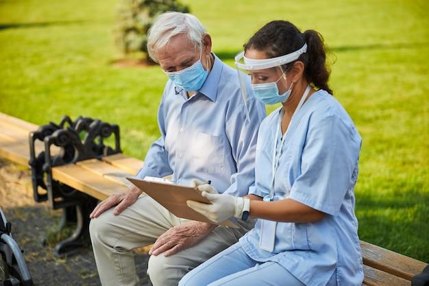 Arzt zeigt notizen zum aktenordner für alten patienten
