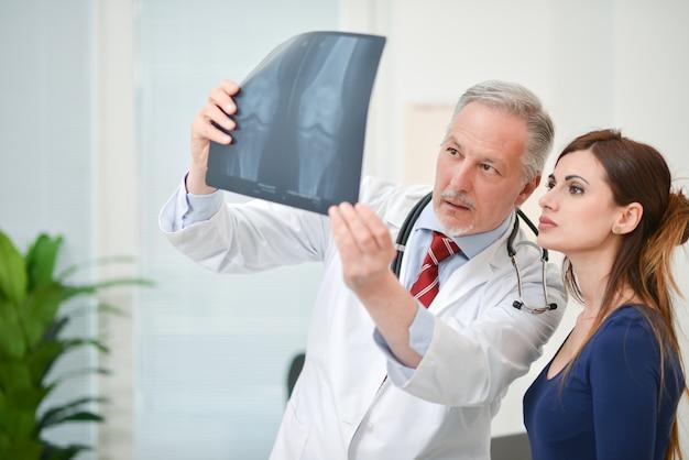 Arzt zeigt seinem patienten eine röntgenaufnahme
