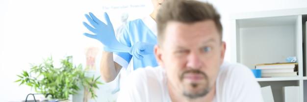 Arzt zieht schutzhandschuh zur rektalen untersuchung des menschen an