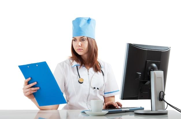 Arztarbeitsplatz am computer, der die ergebnisse des denkens betrachtet