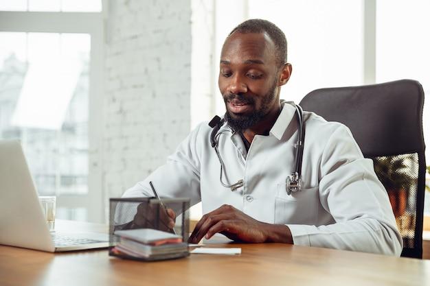 Arztberatung für patienten online, empfehlung. afroamerikanischer arzt während seiner arbeit, der rezepte für medikamente erklärt. tägliche harte arbeit für gesundheit und leben retten während der epidemie.