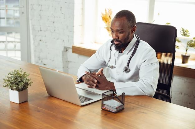 Arztberatung für patienten, ruhig und fröhlich. afroamerikanischer arzt während seiner arbeit mit patienten, der rezepte für medikamente erklärt. tägliche harte arbeit für gesundheit und leben retten während der epidemie.