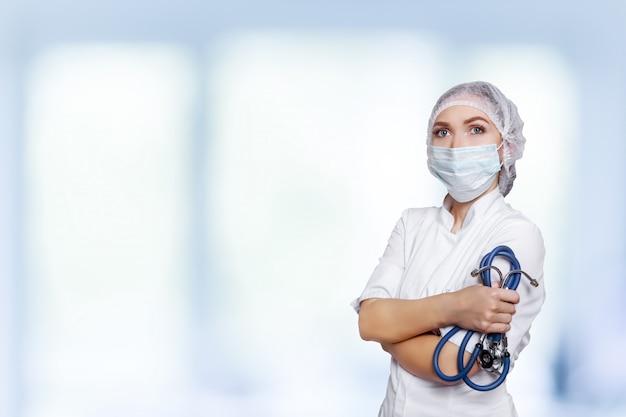 Arztdoktorfrau über blauer klinik