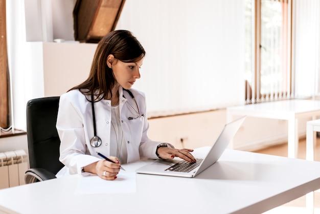 Arztfrau, die an laptop im büro arbeitet