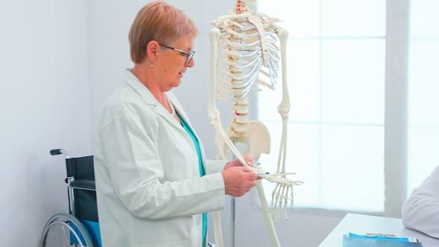Arztfrau, die anatomie unter verwendung des menschlichen skelettmodells unterrichtet, das im krankenhauskonferenzbüro steht. klinikexperte, der mit kollegen über krankheiten spricht, mediziner.