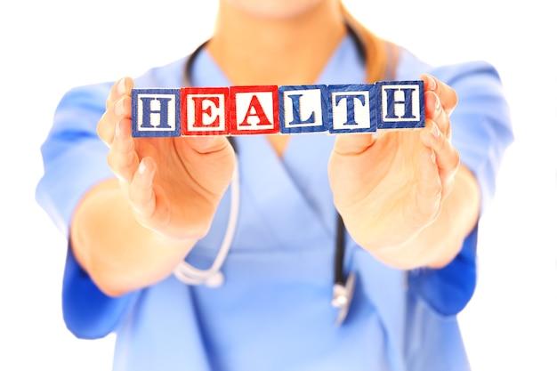Arzthände, die einen gesundheitstext auf holzklötzen auf weißem hintergrund zeigen showing