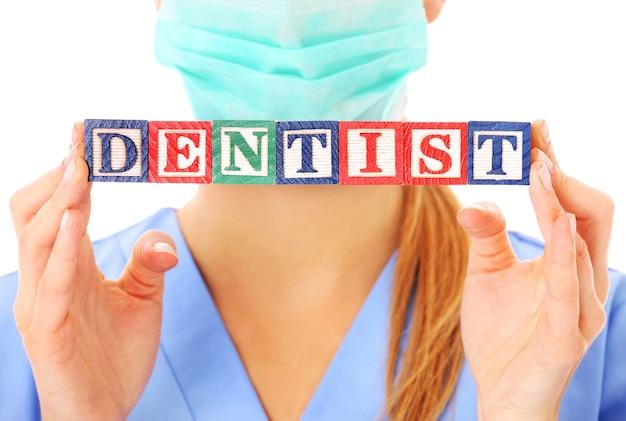 Arzthände, die einen zahnarzttext auf holzklötzen auf weißem hintergrund zeigen