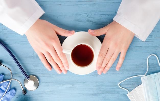 Arzthände mit kaffee am tisch. arztpult.