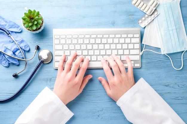 Arzthände und computer auf einem blauen tisch
