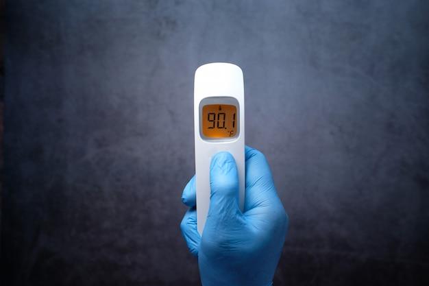 Arzthand mit thermometer temperatur prüfen.