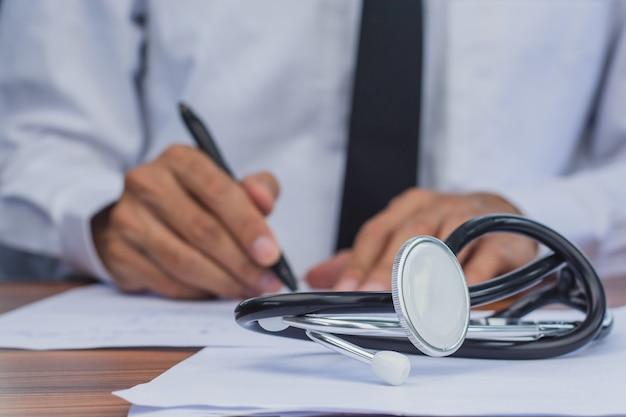 Arzthand unterschreibt die zustimmung des patienten, arzt-stethoskop-testherzfrequenz