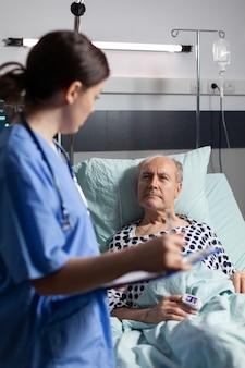 Arzthelferin, die die behandlung des älteren mannes überprüft