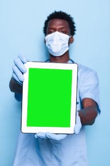Arzthelferin, die vertikalen grünen bildschirm auf tablet hält