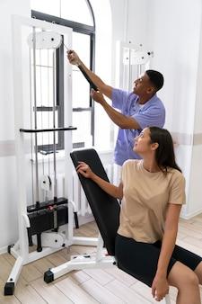 Arzthelferin hilft patienten bei physiotherapieübungen