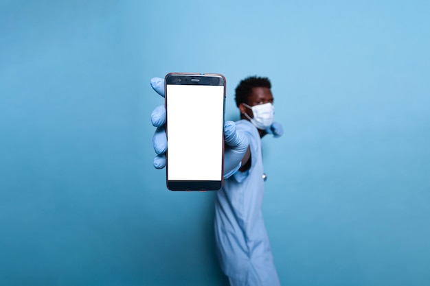 Arzthelferin mit vertikalem leerem bildschirm auf dem smartphone