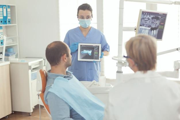 Arzthelferin überprüft zahnröntgenaufnahme an krankem patienten