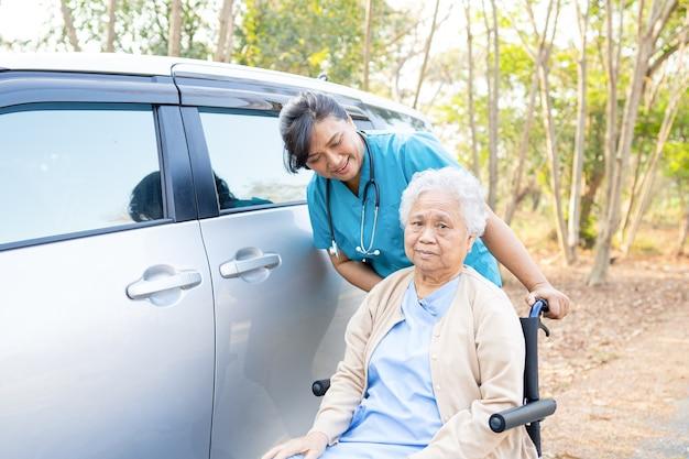 Arzthilfe und pflege asiatische ältere frau patient, die auf rollstuhl im krankenhaus sitzt