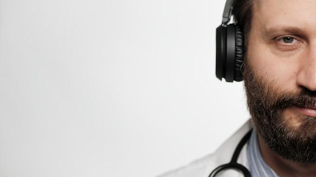 Arztkopfhörer männliches arztgesicht mit kopfhörern auf weißem hintergrund