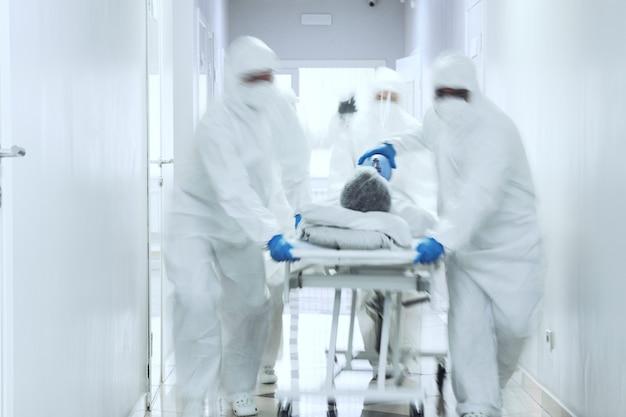 Arztteam in schutzkleidung, das während der coronavirus-pandemie den patienten auf der bahre entlang des korridors trägt