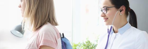 Arzttherapeut hört patientenlunge mit stethoskop-erste-hilfe-konzept