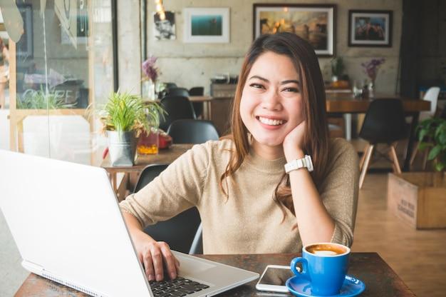 Asain frau, die in der kaffeestube glücklich mit lächeln arbeitet