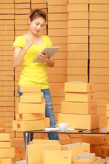 Asain-frau mit tablet-computer, die zu hause im online-shopping-geschäft arbeitet