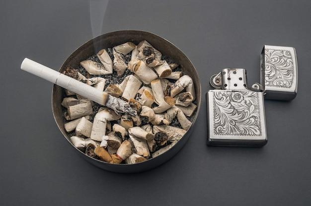 Aschenbecher rauchen zigarettenanzünder auf einem grauen tischhintergrund