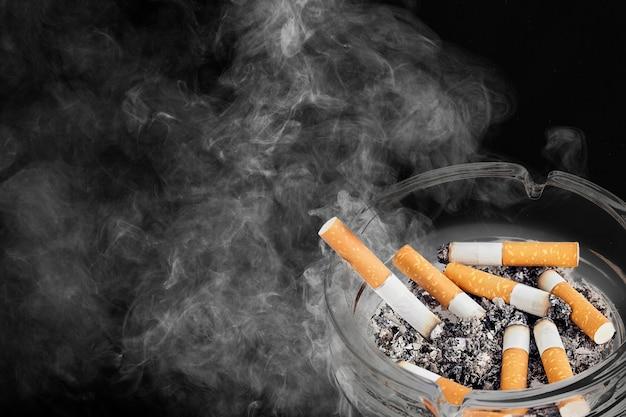 Aschenbecher und gerauchte zigaretten im hintergrund