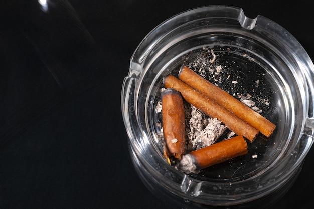Aschenbecher voller zigarettenkippen auf schwarzem hintergrund