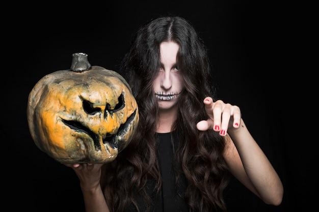 Aschige frau mit der upping hand, die halloween-kürbis hält