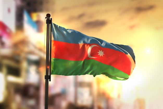 Aserbaidschan flagge gegen stadt verschwommen hintergrund bei sonnenaufgang hintergrundbeleuchtung