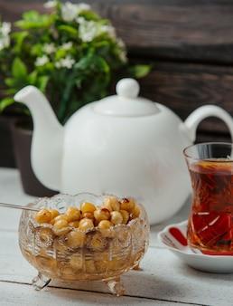 Aserbaidschanische haselnussmarmelade in kristallschale serviert mit schwarzem tee
