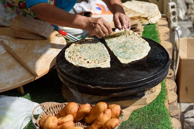 Aserbaidschanische nationalküche - kutabs bei der herstellung. gutab braten in brand