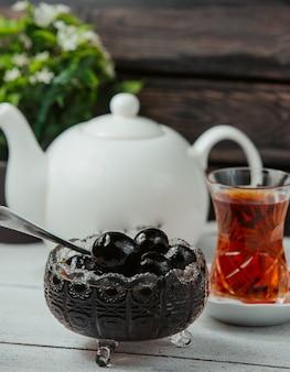 Aserbaidschanische walnussmarmelade in kristallschale serviert mit schwarzem tee