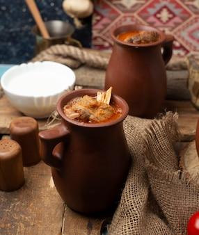 Aserbaidschanischer mahlzeitpiti, fleischeintopfgericht in der tonwarenschale. mit joghurt serviert.