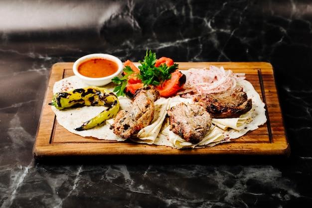 Aserbaidschanischer rindfleisch-barbecue-kebab serviert auf lavash mit gegrilltem pfeffer, tomaten und bbq-sauce.