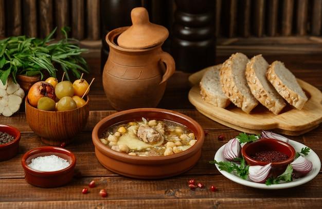 Aserbaidschanisches traditionelles lebensmittel piti in einer tonwarenschüssel diente mit indischem brot